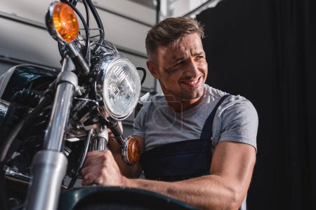 smiling mechanic checking motorcycle front wheel in garage