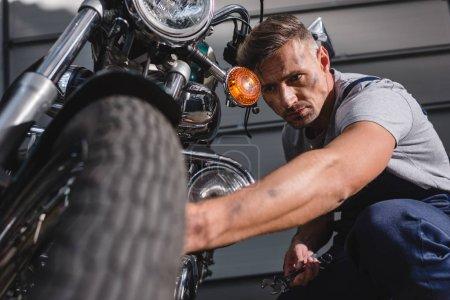 Photo pour Beau adulte mécanicien fixation pneu de moto dans le garage - image libre de droit