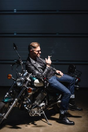 handsome guy in sunglasses leaning on motorcycle in garage