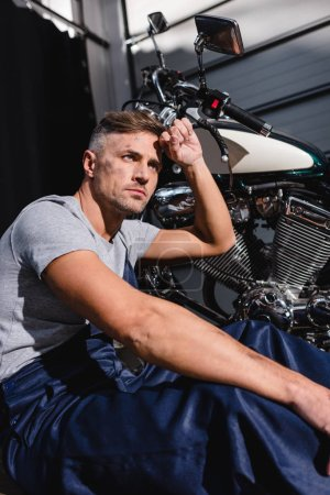 mechanic with hand on forehead next to motorbike in garage