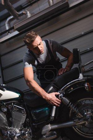 serious mechanic checking back wheel in garage