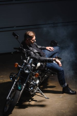 side view of handsome guy in sunglasses sitting on motorcycle in garage