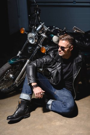 handsome biker in sunglasses sitting by motorcycle in garage