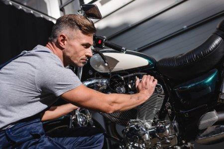 mechanic checking motorbike engine in garage