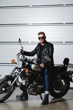 Photo pour Bel homme en lunettes de soleil assis sur la moto et regardant la caméra - image libre de droit