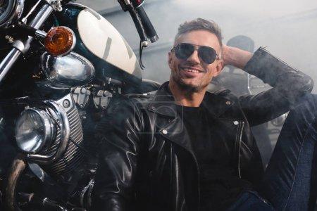 Photo pour Bel homme aux lunettes de soleil souriant assis à moto dans le garage - image libre de droit