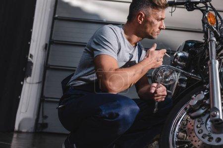 mechanic checking motorcycle front wheel and smoking in garage
