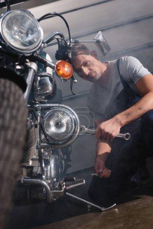 Photo pour Beau mécanicien tenant une clé et fixation moteur de moto dans le garage - image libre de droit