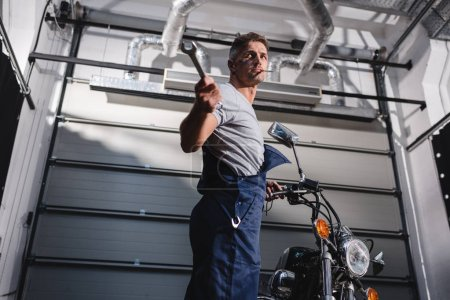 mechanic holding wrench and fixing motorbike in garage