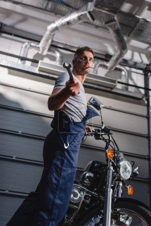 Photo pour Mécanicien avec clé en main à côté de la moto au garage - image libre de droit