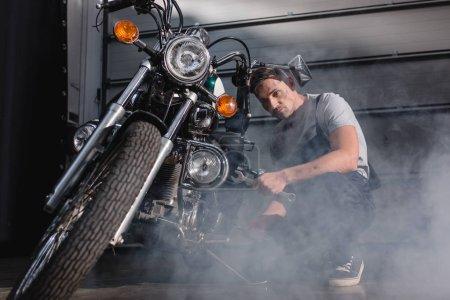 mechanic fixing motorcycle front wheel in garage