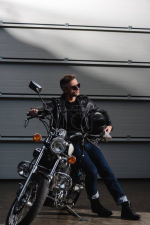classic rider in black sunglasses and leather jacket standing by motorcycle in garage