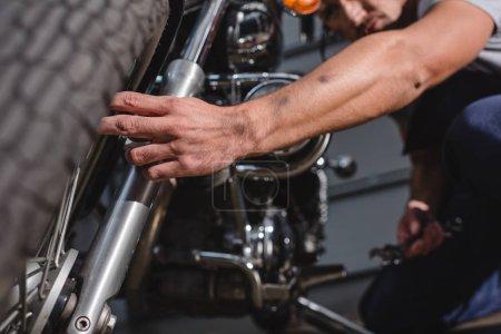 closeup of mechanic fixing motorbike front wheel in garage