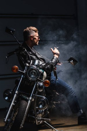 classic stylish rider in sunglasses leaning on motorcycle in garage