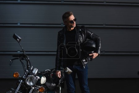 handsome biker in sunglasses holding helment and standing by motorcycle in garage