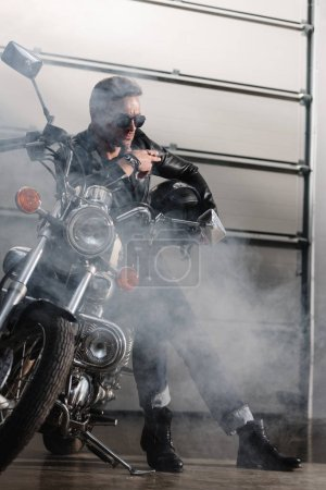 handsome rider in black sunglasses leaning on motorcycle in garage