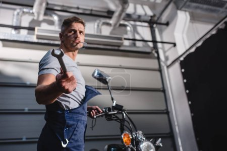 mechanic smoking cigarette and holding wrench