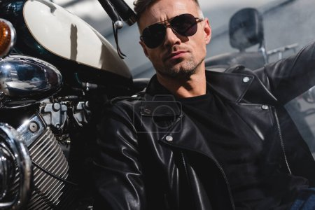 Photo for Handsome classic guy in sunglasses sitting by motorcycle in garage - Royalty Free Image