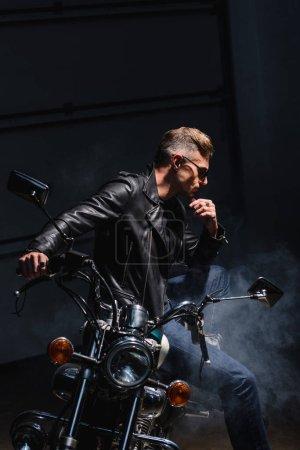 Photo pour Motard classique en lunettes de soleil assis sur la moto dans le garage - image libre de droit
