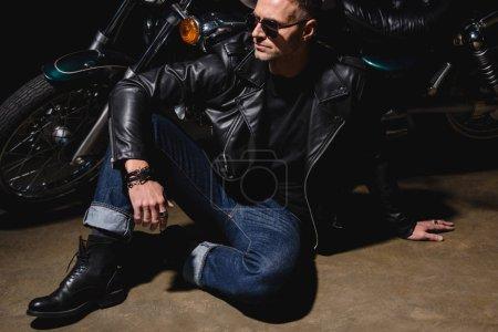 man in black sunglasses sitting by motorcycle in garage