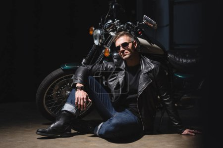 handsome biker in sunglasses standing by motorcycle in garage