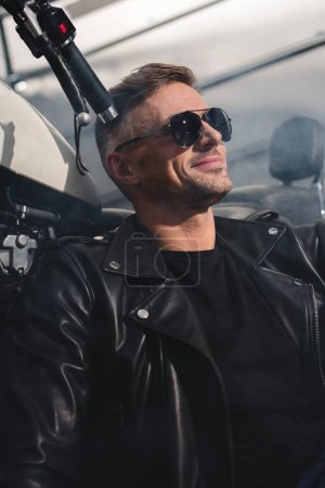 handsome motorbiker in black sunglasses smiling and sitting by motorbike in garage