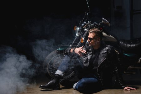 handsome biker in black sunglasses sitting on floor next to motorcycle in garage