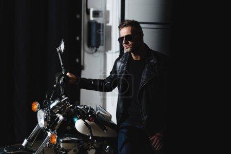 stylish man in black sunglasses posing by motorbike in garage