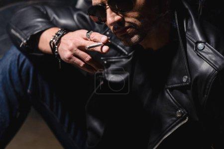 Photo pour Bel homme en lunettes de soleil noires et veste en cuir appuyé sur la moto - image libre de droit