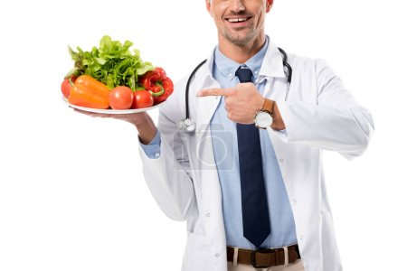 cropped view of doctor pointing with finger at plate of fresh vegetables isolated on white, healthy eating concept