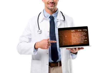 cropped view of smiling doctor pointing finger at laptop with health data on screen isolated on white