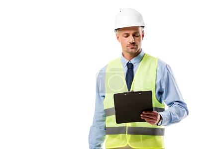 focused engineer in helmet looking at clipboard isolated on white