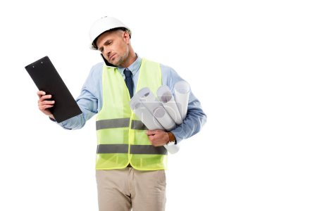 handsome engineer holding blueprints, talking on smartphone and looking at clipboard isolated on white