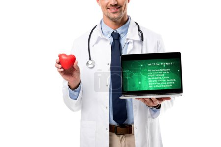 cropped view of smiling doctor holding heart model and laptop with health data on screen isolated on white, heart healthcare concept
