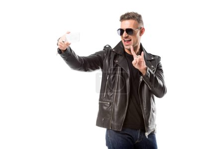 Photo for Excited adult man in sunglasses showing rock sign and taking selfie on smartphone isolated on white - Royalty Free Image