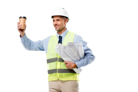 smiling engineer in safety vest holding blueprints and coffee to go isolated on white