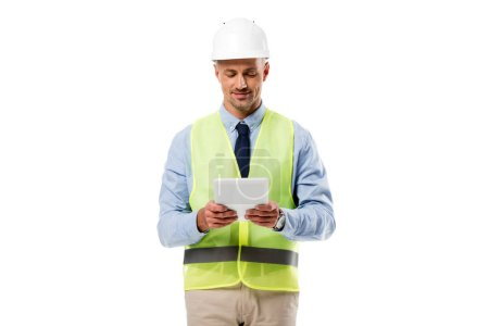 Photo for Engineer in helmet smiling and using digital tablet isolated on white - Royalty Free Image