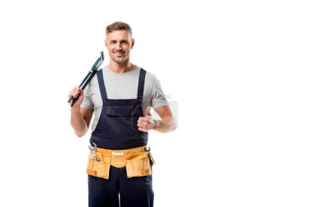 smiling plumber holding pipe wrench and showing thumb up sign isolated on white
