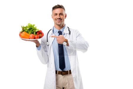 Photo for Smiling doctor pointing with finger at plate of fresh vegetables and greenery isolated on white, healthy eating concept - Royalty Free Image