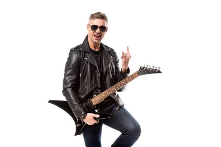 excited adult man in leather jacket holding electric guitar and showing rock sign isolated on white