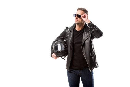 Photo for Man in leather jacket and sunglasses holding motorcycle helmet and posing isolated on white - Royalty Free Image