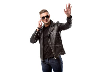 handsome man in sunglasses talking on smartphone, waving to someone and looking away isolated on white