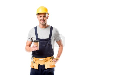 smiling construction worker in helmet drinking coffee to go isolated on white