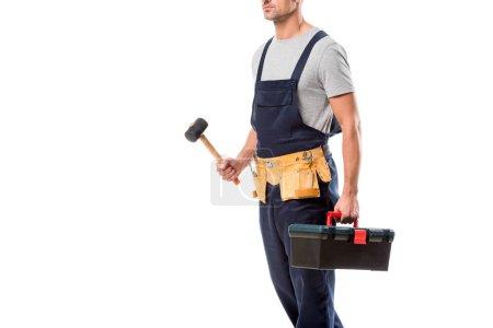 abgeschnittene Ansicht eines Bauarbeiters, der Hammer und Werkzeugkiste isoliert auf Weiß hält