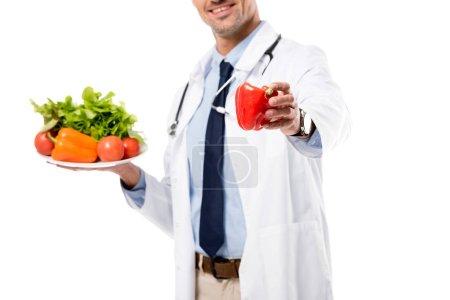 Foto de Vista recortada de médico con pimienta y plato de verduras frescas con verde aislado en blanco, sano concepto comer - Imagen libre de derechos
