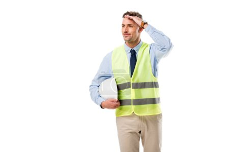 handsome engineer in safety vest holding helmet and touching forehead isolated on white