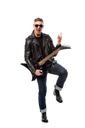 excited stylish man in leather jacket holding electric guitar and showing rock sign isolated on white