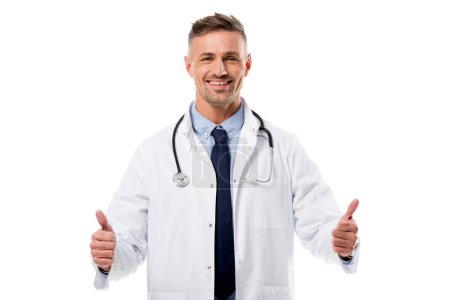 Photo for Smiling doctor in white coat with stethoscope doing thumbs up sign isolated on white - Royalty Free Image