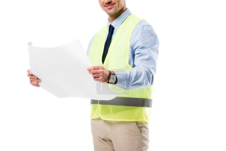cropped view of smiling engineer in safety vest holding blueprint isolated on white