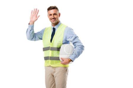Foto de Sonriendo holding casco de Ingeniero, saludando y mirando a cámara aislada en blanco - Imagen libre de derechos